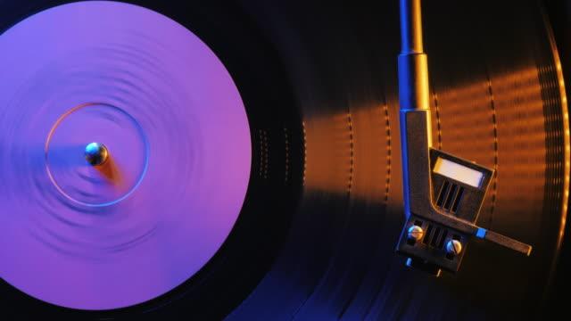vídeos de stock, filmes e b-roll de aparência de filme estilo retrô de um jogador de discos de vinil de fiação. close-up. 4k, timelapse, vista superior. filme colorido com luz de neon - dj
