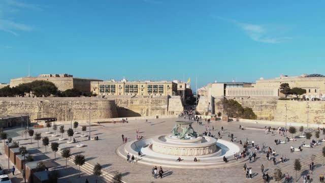 Reveal of Triton Fountain and St. John's Bastion, Valletta , Malta, Aerial forward