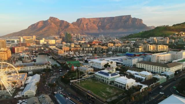 Revealing Cape Town's V&A Waterfront Aerial shot of camera flying backwards revealing the V&A Waterfront and the Table Bay coast line with Table Mountain in the background. cape town stock videos & royalty-free footage