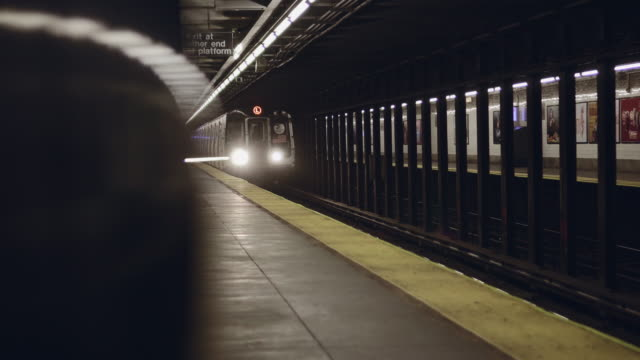 Revealing shot of New York City subway train arriving to the underground station