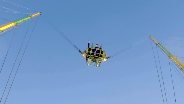 reverse bungee with blue sky at amusement park in slow motion - bungee jumping video stock e b–roll