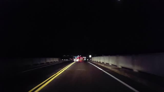 *Reverse Motion* Driving From City Lights on Horizon to Rural Countryside Backward.  Driving Point of View POV Leaving Urban Street Toward Country Road.