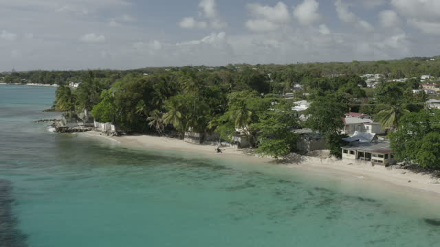 Reverse tracking drone shot of tropical beach/bar scene (2) (offset angle) video