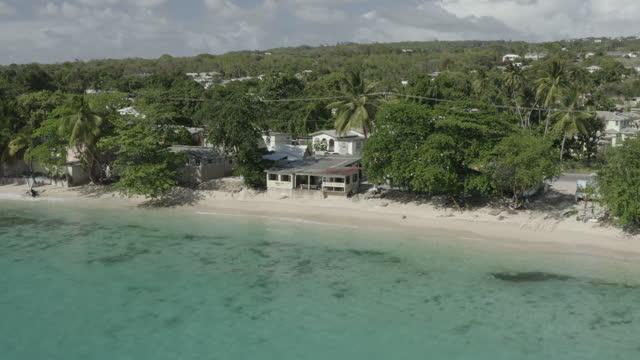 Reverse tracking drone shot of tropical beach/bar scene (1) video