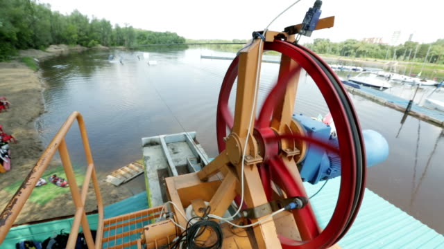 Reversible winch closeup. In the background wakeboarder rides video