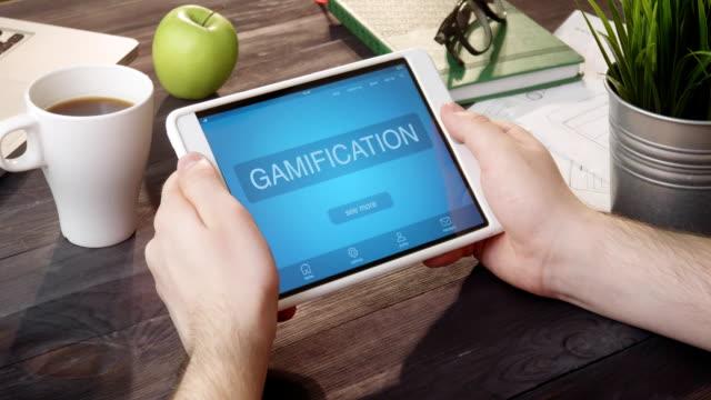vídeos de stock e filmes b-roll de reviewing gamification app using portable computer at desk - badge