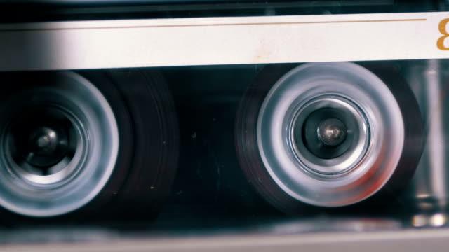 rewind an audio cassette tape inserted into a tape recorder - cassetta video stock e b–roll