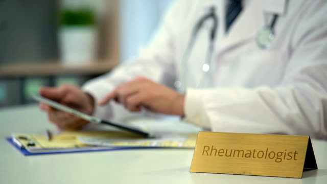 Rheumatologist searching medical records on tablet, consulting patient online video