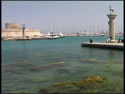 rhodes, greece: harbor entrance with brass deers and fort walls - egeiska havet bildbanksvideor och videomaterial från bakom kulisserna