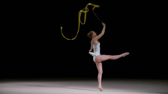 SLO MO LD Rhythmic gymnast doing a jump while swirling a golden ribbon