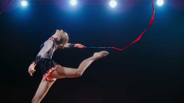 slo mo ld rhythmic gymnast doing a leap with her head leaned back while swirling her red ribbon - flessibilità video stock e b–roll