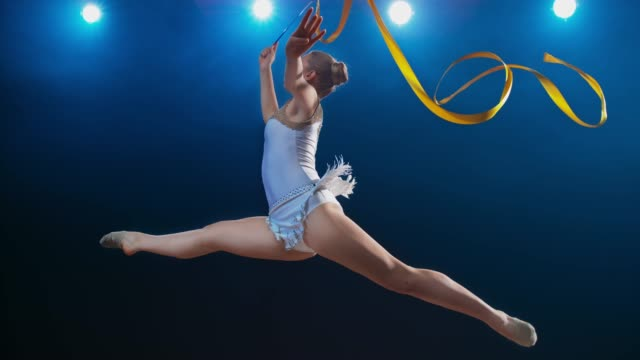 SLO MO LD Rhythmic gymnast doing a scissor leap while swirling her golden ribbon