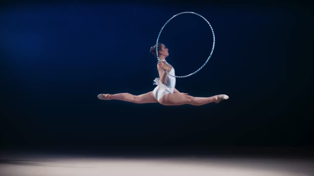 SLO MO LD Rhythmic gymnast doing a split leap while rotating a hoop around her hand