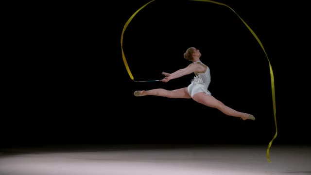 SLO MO LD Rhythmic gymnast doing a split leap while swirling her ribbon