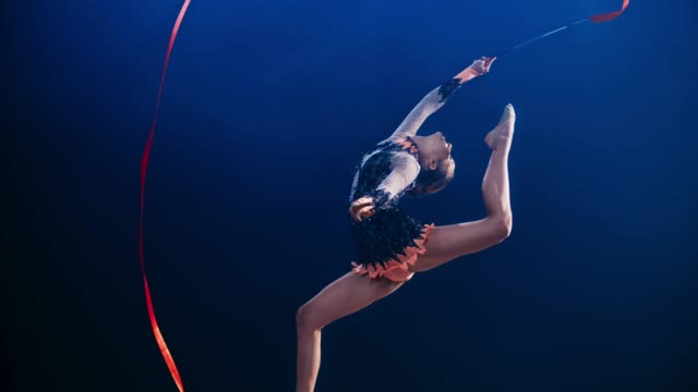 SLO MO Rhythmic gymnast doing a stag leap and rotating her red ribbon above her head