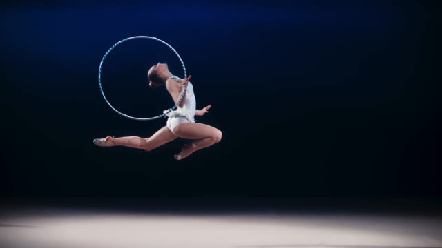 SLO MO LD Rhythmic gymnast doing a stag leap while rotating a hoop around her hand
