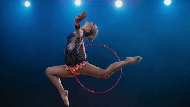 SLO MO LD Rhythmic gymnast doing a stag leap while rotating her hoop