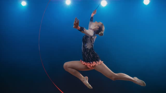 SLO MO LD Rhythmic gymnast doing a stag leap while swirling her red ribbon