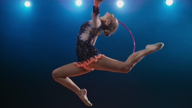 SLO MO SPEED RAMP LD Rhythmic gymnast doing a stag leap with a hoop rotating around her hand