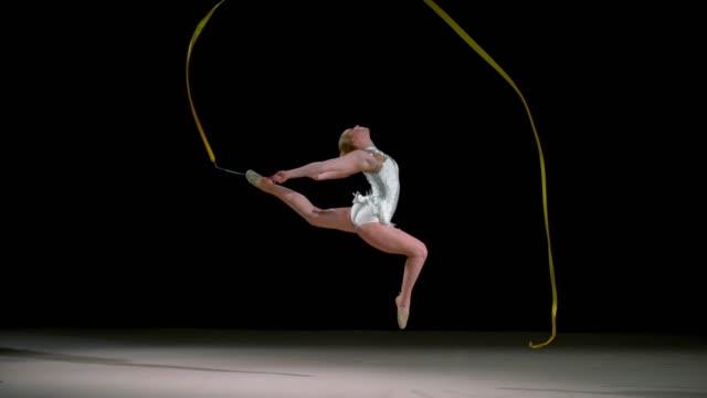 SLO MO SPEED RAMP LD Rhythmic gymnast jumping while waving a ribbon across the air