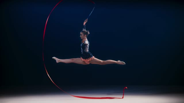 SLO MO Rhythmic gymnast moving her ribbon in a large circle while doing a leap