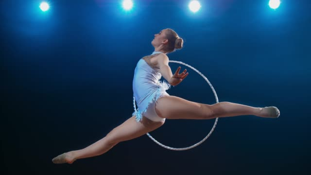 SLO MO LD Rhythmic gymnast performing a scissor leap while rotating her hoop