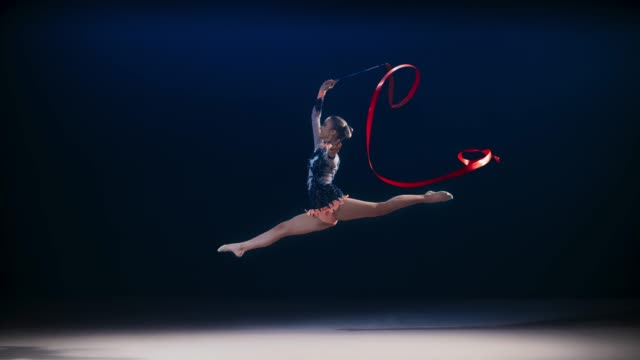 SLO MO LD Rhythmic gymnast performing a scissor leap while swirling a red ribbon above her Slow motion wide locked down shot of a rhythmic gymnast in a black leotard performing a scissor leap and swirling a red ribbon above her head. Shot in Slovenia. doing the splits stock videos & royalty-free footage