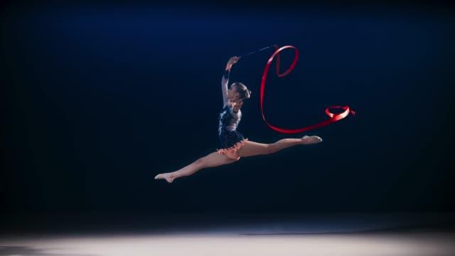 vídeos y material grabado en eventos de stock de slo mo ld gimnasta rítmica realizando un salto de tijera mientras se arremodela una cinta roja por encima de su - gimnasia