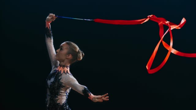 SLO MO Rhythmic gymnast performing a scissor leap while swirling a red ribbon