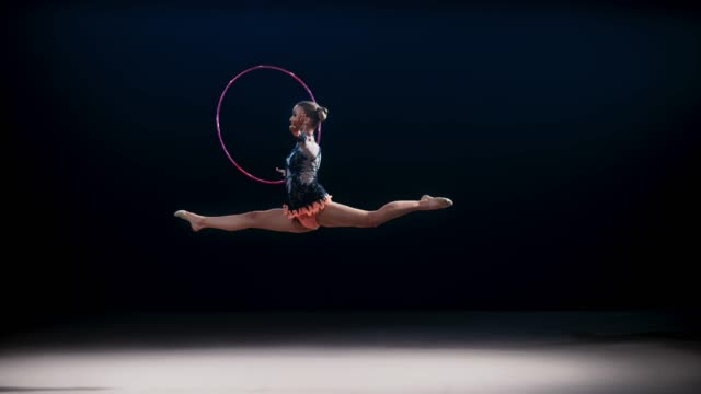 SLO MO LD Rhythmic gymnast performing a split jump while rotating a violet hoop in her hand