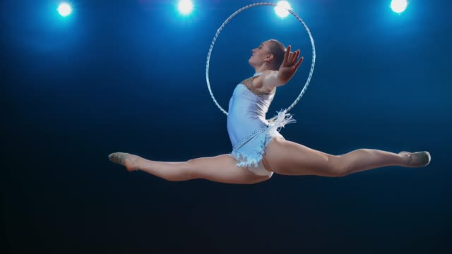 SLO MO SPEED RAMP LD Rhythmic gymnast performing a split leap while rotating her hoop in one hand