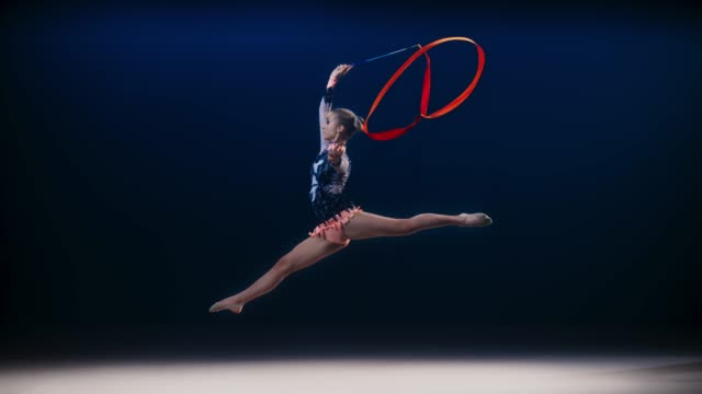 SLO MO LD Rhythmic gymnast performing a split leap while swirling a red ribbon