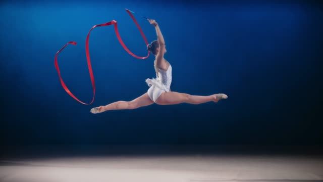 SLO MO LD Rhythmic gymnast performing a split leap with a red ribbon swirling in her hand