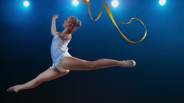 SLO MO SPEED RAMP LD Rhythmic gymnast performing a split leap with her ribbon swirling in the air