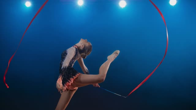 SLO MO LD Rhythmic gymnast performing a stag leap while making a large circle with her red ribbon