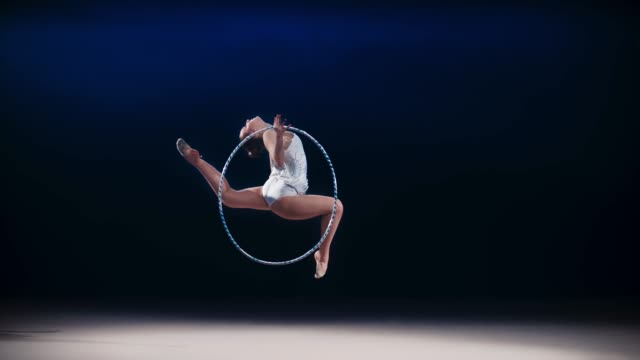 SLO MO LD Rhythmic gymnast performing a stag leap while rotating a hoop in her hand