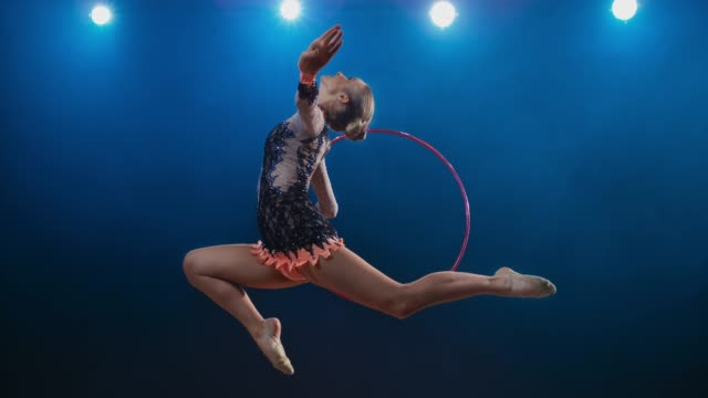 SLO MO LD Rhythmic gymnast performing a stag leap while rotating her hoop