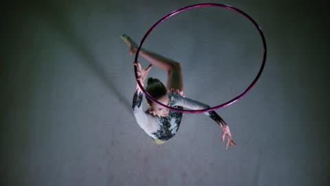 vidéos et rushes de slo mo ld gymnaste rythmique tournant un cerceau au-dessus de sa tête tandis que dans un pivot - exactitude