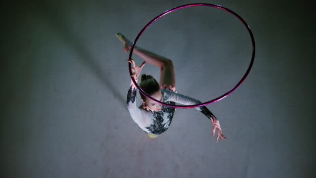 SLO MO LD Rhythmic gymnast rotating a hoop above her head while in a pivot Slow motion wide right above locked down shot of a rhythmic gymnast performing an elegant pivot and rotating her hoop above the head. Shot in Slovenia. performer stock videos & royalty-free footage