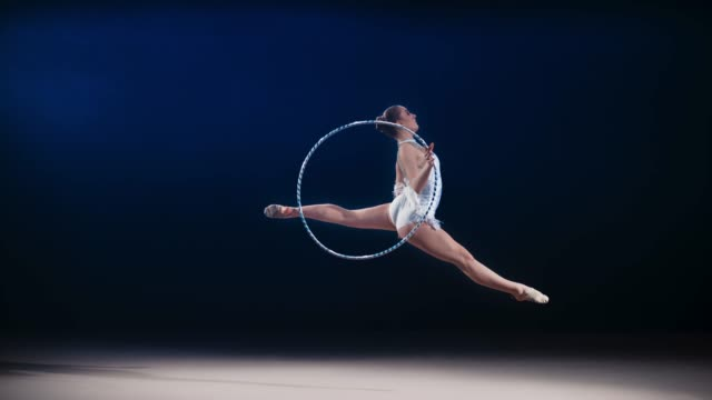 SLO MO SPEED RAMP LD Rhythmic gymnast rotating a hoop around her hand during a leap