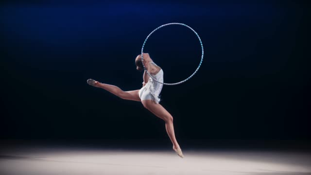 SLO MO SPEED RAMP LD Rhythmic gymnast rotating a hoop around her hand during a stag leap