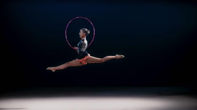 SLO MO SPEED RAMP LD Rhythmic gymnast rotating her hoop and performing a split leap