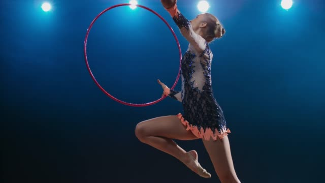 SLO MO LD Rhythmic gymnast rotating her hoop and performing a stag leap