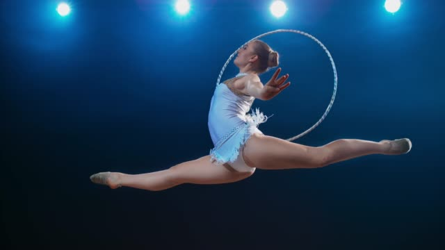 SLO MO LD Rhythmic gymnast rotating her hoop while performing a stag leap Slow motion wide low angle locked down shot of a rhythmic gymnast rotating her hoop while performing a stag leap under the spotlights. Shot in Slovenia. leotard stock videos & royalty-free footage