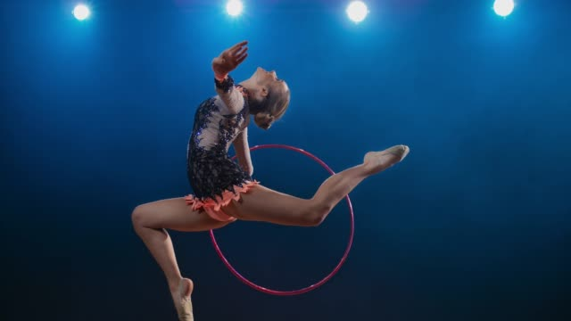 SLO MO SPEED RAMP LD Rhythmic gymnast rotating her hoop while performing the stag leap