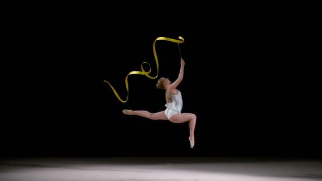 SLO MO LD Rhythmic gymnast running across the floor and swirling a ribbon