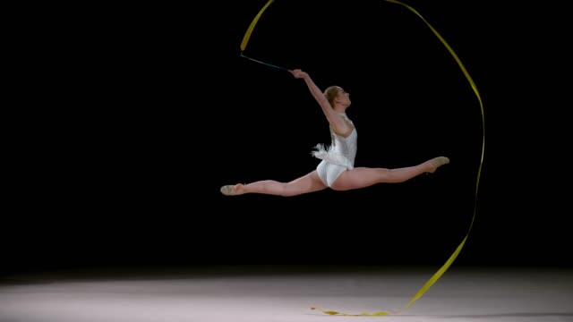 SLO MO SPEED RAMP LD Rhythmic gymnast running across the floor doing a leap and swirling the golden ribbon