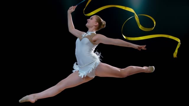 slo mo rhythmic gymnast smiling while performing a split jump with a swirling golden ribbon - agilità video stock e b–roll