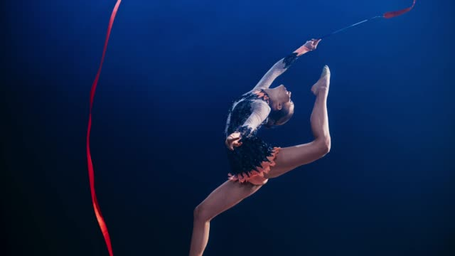 slo mo speed ramp rhythmic gymnast swinging her red ribbon above her head while doing a stag leap - agilità video stock e b–roll