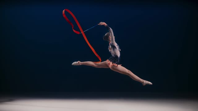 SLO MO SPEED RAMP LD Rhythmic gymnast swirling a red ribbon above her head during a split leap